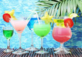 Glasses of cocktails on table on blue sea background — Stock Photo