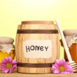 Stock Photo: Sweet honey in barrel and jars with drizzler on wooden table on green background