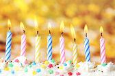 Beautiful birthday candles on yellow background — Stock Photo