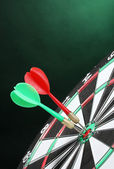 Dart board with darts on green background — Photo