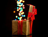 Open golden gift box with bokeh background on black — Stock Photo