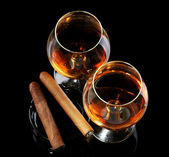Two glasses of brandy and cigars on black background — Photo