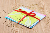 Bunch of color envelopes with ribbon and confetti on wooden background — Stock Photo