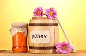 Słodki miód w beczki i słoik z drizzler na drewnianym stole na żółtym tle — Zdjęcie stockowe