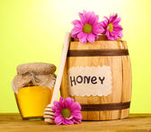 Sweet honey in barrel and jar with drizzler on wooden table on green background — Stock fotografie