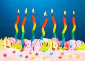 Tort urodzinowy z świece na niebieskim tle — Zdjęcie stockowe