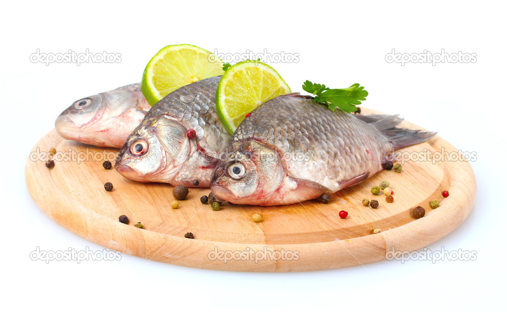 Fresh fishes with lime, parsley and spice on wooden cutting board isolated on white — Stock Photo #9915465