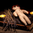 Voodoo doll girl on wooden table in candlelight — Zdjęcie stockowe #9940388