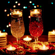 Amazing composition of candles and glasses on wooden table on bright background — Stock Photo #9940525