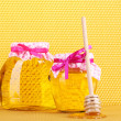 Jars of honey and wooden drizzler on yellow honeycomb background — Stock Photo #9949777