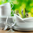 Clean dishes on wooden table on green background — 图库照片