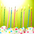Stock Photo: Beautiful birthday candles on green background