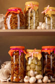 Delicious marinated mushrooms in the glass jars, raw champignons and oyster mushrooms on wooden shelfs — Stock Photo