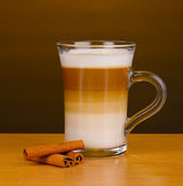 Fragrant сappuccino latte in glass cup and cinnamon on wooden table on brown background — Stock Photo