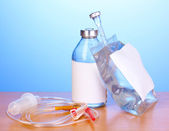 Bottle and bag of intravenous antibiotics and plastic infusion set on wooden table on blue background — Stock Photo