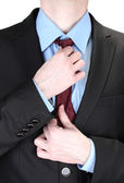 Businessman correcting a tie close up — Stock Photo