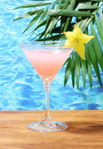 Glass of cocktail on blue sea background — Stock Photo