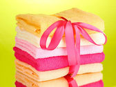 Colorful towels with ribbon on green background — Stock Photo