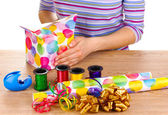 Wrapping presents surrounded by paper, ribbon and bows — Stockfoto