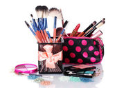 Make-up brushes in holder and cosmetics isolated on white — Stock Photo