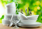 Clean dishes on wooden table on green background — Stockfoto