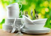 Czyste naczynia na drewnianym stole na zielonym tle — Zdjęcie stockowe