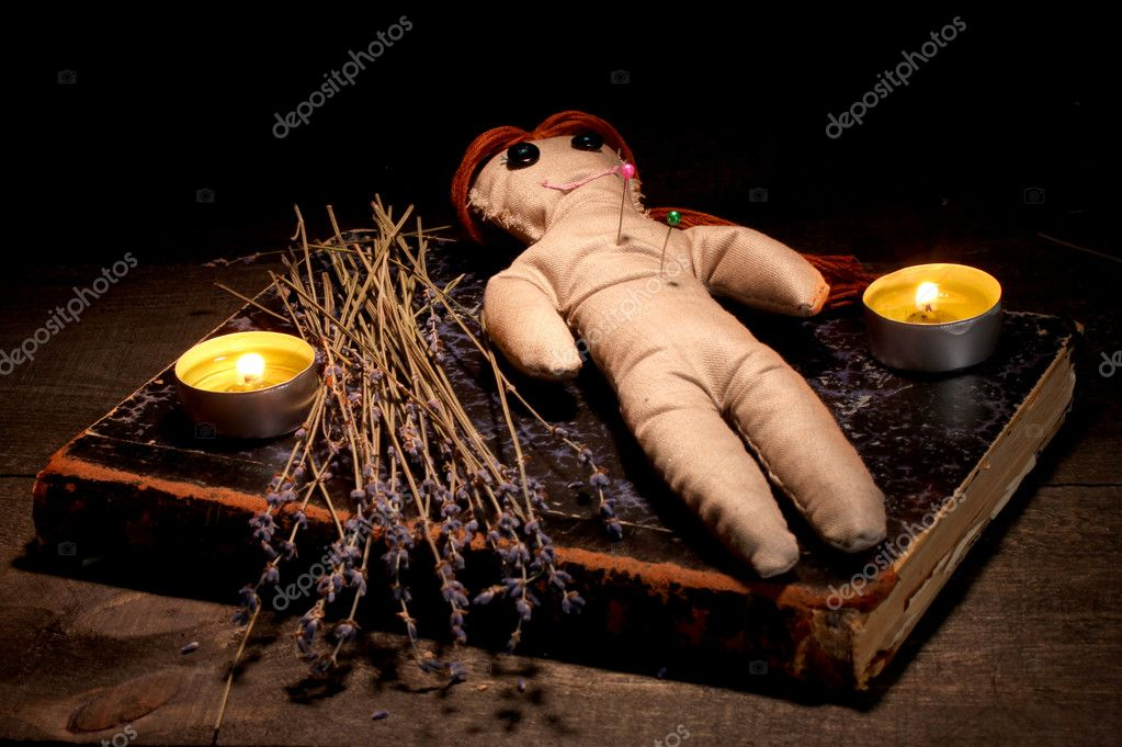 Voodoo doll girl on a wooden table in the candlelight — Stockfoto #9940388