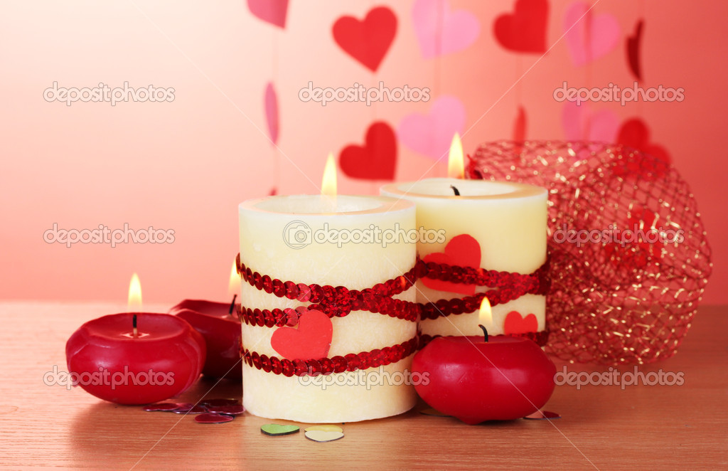 Candles for Valentine's Day on wooden table on red background — Stock Photo #9949819