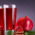 Ripe pomergranate and glasses of juice on purple background — Stock Photo