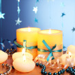 Beautiful candles, gifts and decor on wooden table on blue background — Stock Photo #9965825