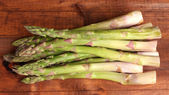 Delicious asparagus on wooden background — Stock Photo