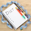 Planning of diet. Notebook measuring tape and pen on wooden table — Stock Photo #9984893