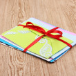 Bunch of color envelopes with ribbon on wooden background — Stock Photo