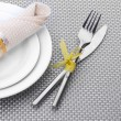 White empty plates with fork and knife tied with a ribbon on a grey tablecloth — Stock Photo