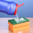 Stock Photo: Sponge with scouring powder on wooden table on blue background