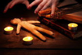 Voodoo doll boy on a wooden table in the candlelight — ストック写真