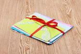 Bunch of color envelopes with ribbon on wooden background — Fotografia Stock