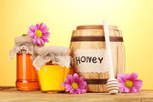 Sweet honey in barrel and jars with drizzler on wooden table on yellow background — Stock Photo