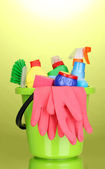 Bucket with cleaning items on green background — Stock Photo
