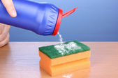 Sponge with scouring powder on wooden table on blue background — Stock Photo