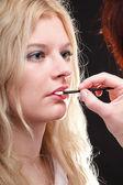 Beautiful woman putting on makeup — Stock Photo