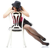 Showgirl woman dance in red corset chair white isolated — Stockfoto
