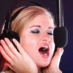 Woman singing rock song microphone headphones — Stock Photo