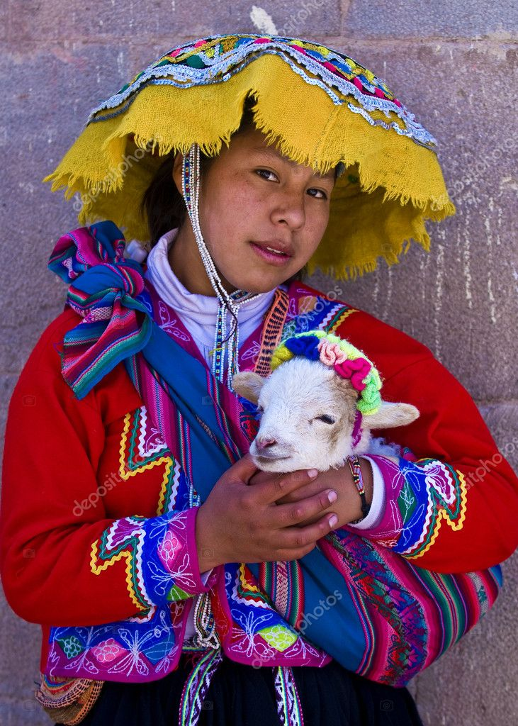CUSCO , PERU - MAY 27 2011 : Unidentified Peruvian girl in traditional colorful clothes holding a lamb in here arms in the  Unesco world heritage city Cusco — Stock Photo #8745240