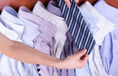 Men's hands hold the tie over shirts — Stock Photo
