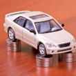 Stock Photo: Model car on a pile of coins