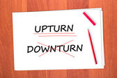 Chose the word UPTURN, crossed out the word DOWNTURN — Stock Photo