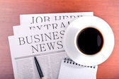 Business newspaper, notebook and cup of coffee — Stock Photo