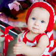 Cute little girl in a red cap with a New Year gift — Stock Photo #10598446