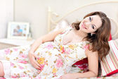 Pretty pregnant girl sitting on a bed — Stock Photo